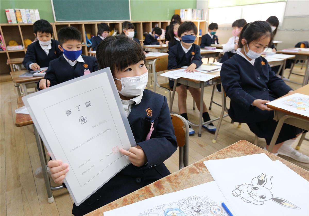 修了証を受け取り、うれしそうに掲げる児童=24日午前、大阪市生野区の巽小学校(一部画像処理しています、寺口純平撮影)