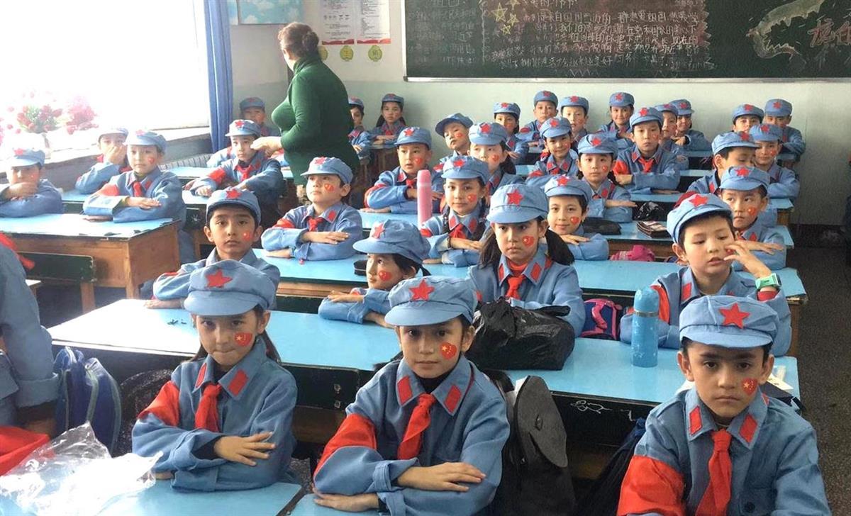 中国の軍服を着用して授業を受けるウイグル人の子供たち。現地では「中国化」が進む(日本ウイグル協会提供)