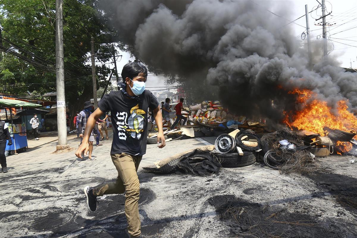 28日、ミャンマー・ヤンゴンで、防衛のために燃やしたバリケードの近くを走る反軍政デモの参加者(AP=共同)