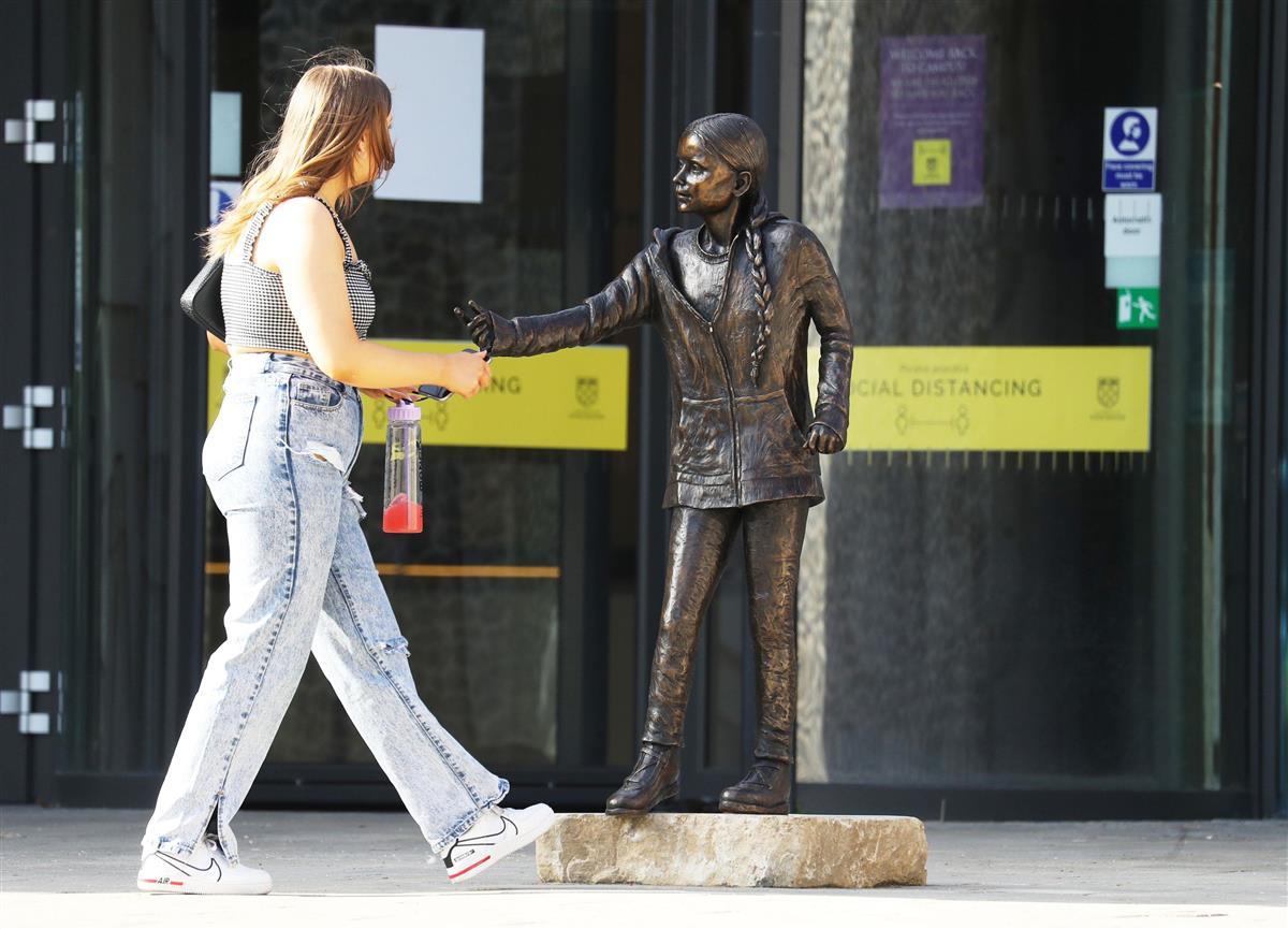 英南部ウィンチェスター大に設置されたグレタ・トゥンベリさんの銅像と近くを歩く人=30日(英PA通信=共同)