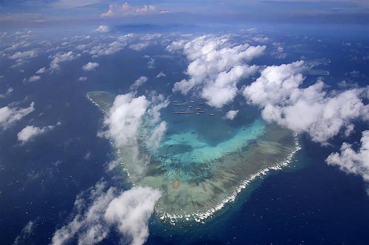 南シナ海・南沙諸島のサンゴ礁のくぼみ部分に集まる中国漁船=3月22日(フィリピン国軍提供・共同)