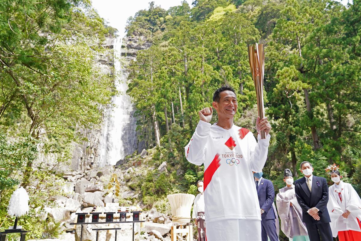 聖火リレーで那智の滝を背に笑顔を見せる西山等さん=9日午前、和歌山県那智勝浦町(沢野貴信撮影)