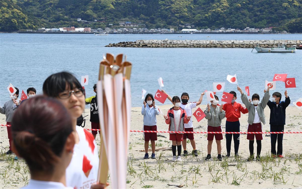 日本とトルコの国旗を振りながら聖火をつなぐ場面を見つめる地元の小学生ら=9日午後、和歌山県串本町(永田直也撮影)