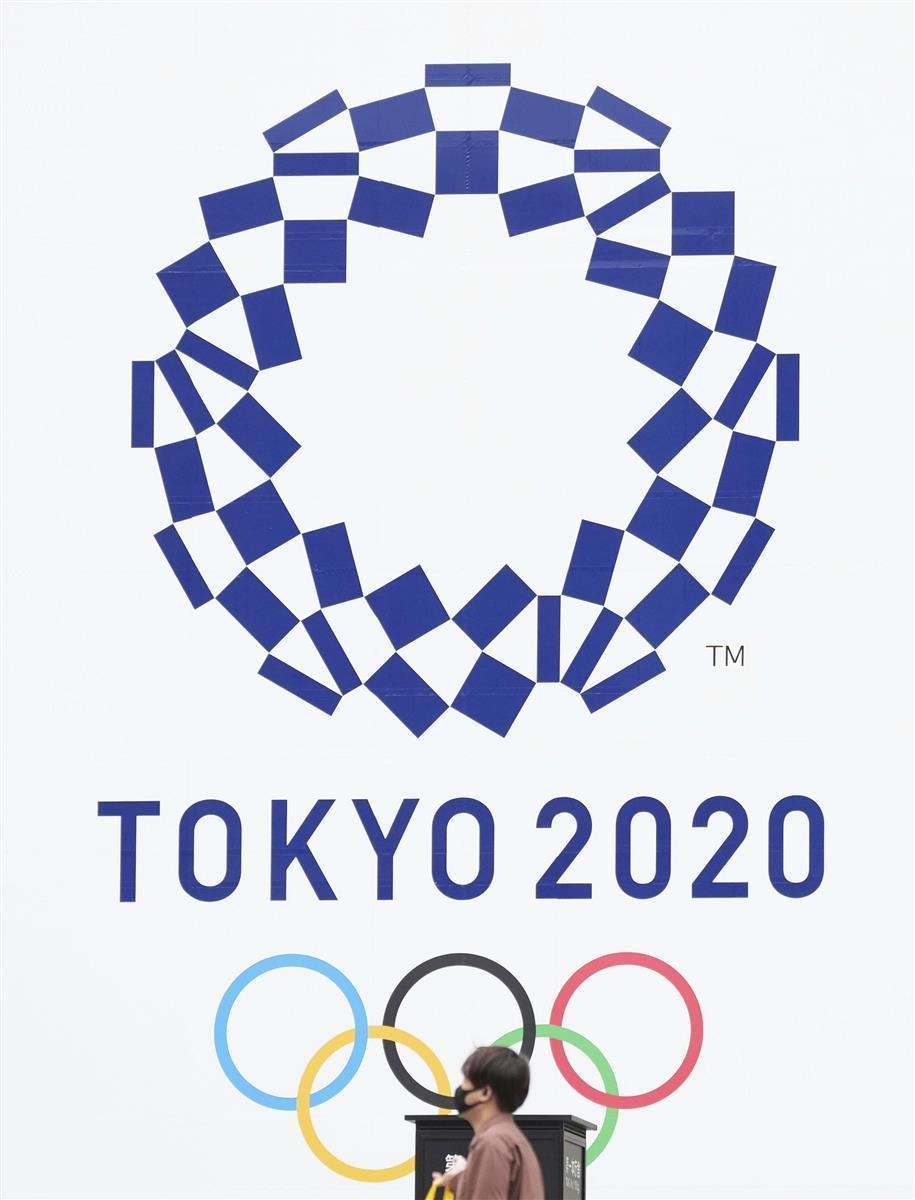 東京都庁の壁面に掲示された東京五輪の公式エンブレム=13日午後