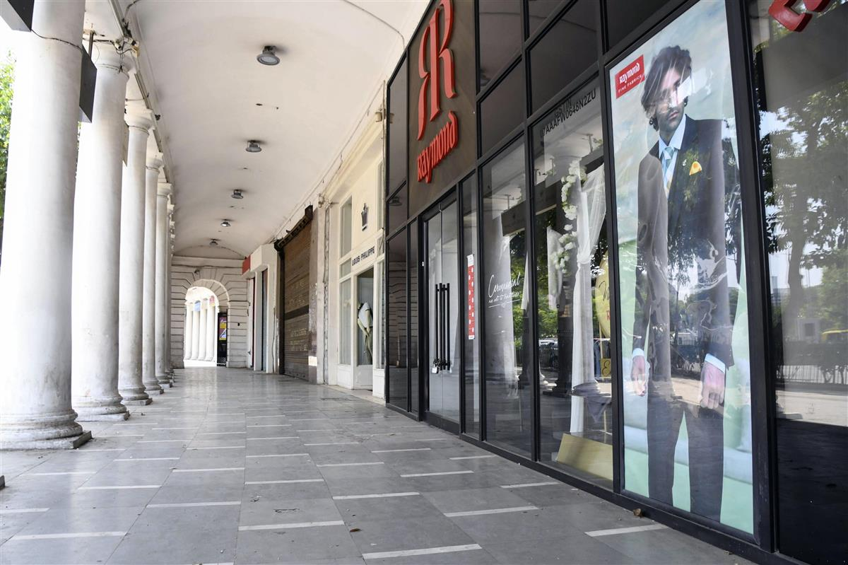 17日、週末の外出禁止令のため人通りが途絶えた、インドの首都ニューデリーの商店街(共同)
