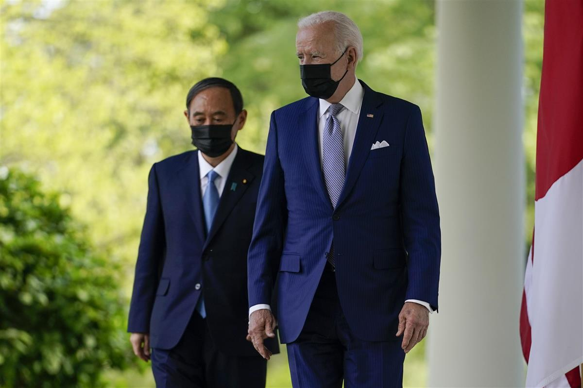 共同記者会見に向かうバイデン米大統領(右)と菅首相=16日、ワシントンのホワイトハウス(AP)