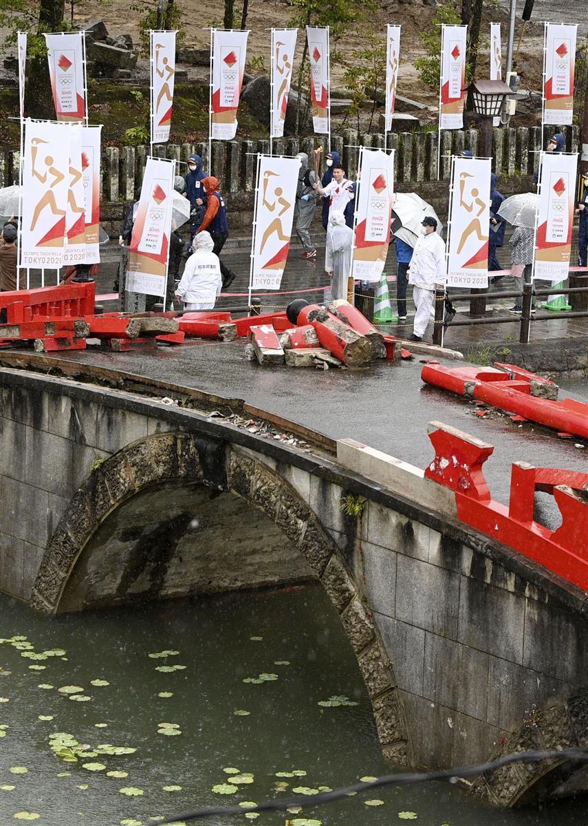 昨年7月の豪雨で被害を受けた青井阿蘇神社を走る聖火ランナー。橋の欄干は壊れたまま=5日午前、熊本県人吉市