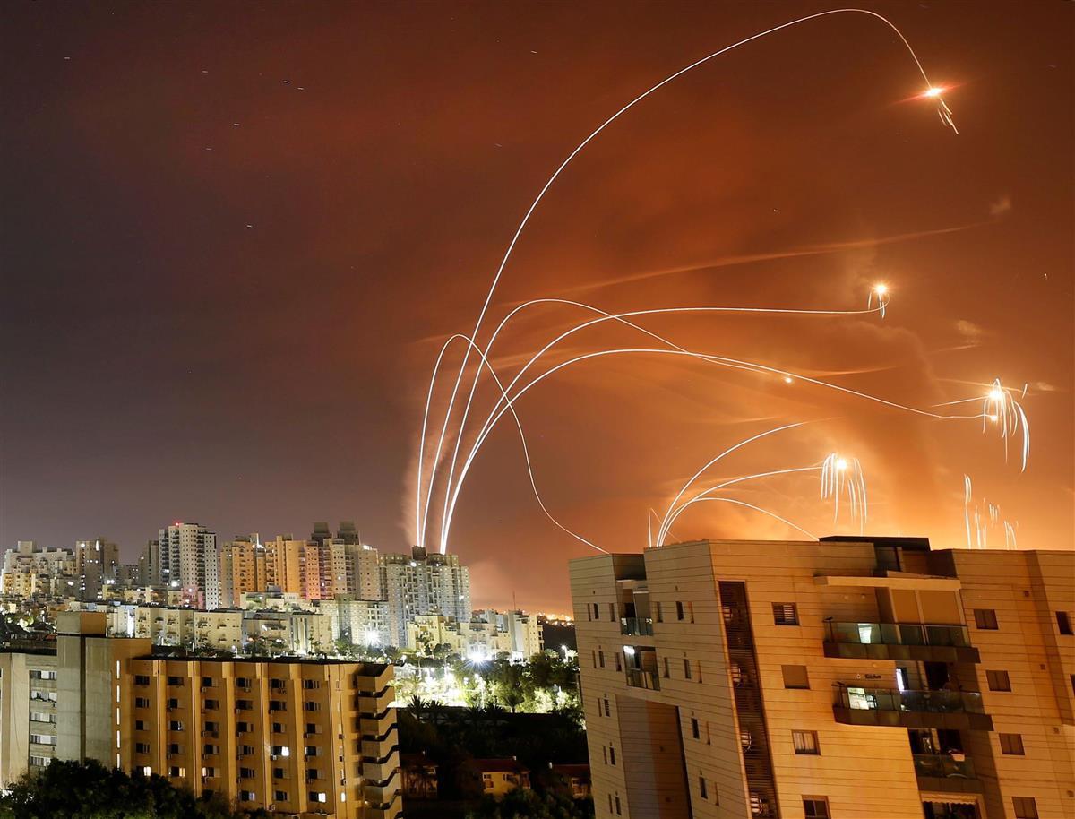 ガザ地区から発射されたロケット弾と、それを迎撃する防空システム「アイアンドーム」の光跡=12日、イスラエル中部アシュケロン近郊(ロイター)