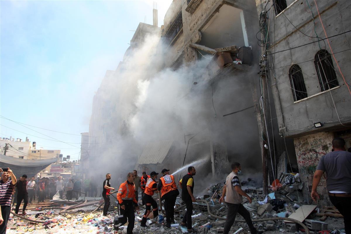 15日、イスラエルの攻撃を受けたパレスチナ自治区ガザ南部の建物に駆け付けた消防士ら(UPI=共同)
