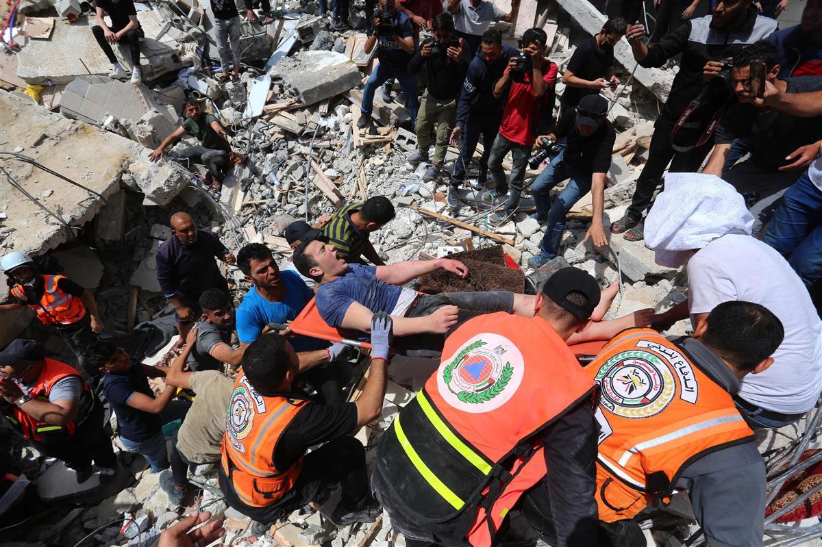 16日、パレスチナ自治区ガザで、空爆により破壊された建物から救助される男性(ゲッティ=共同)