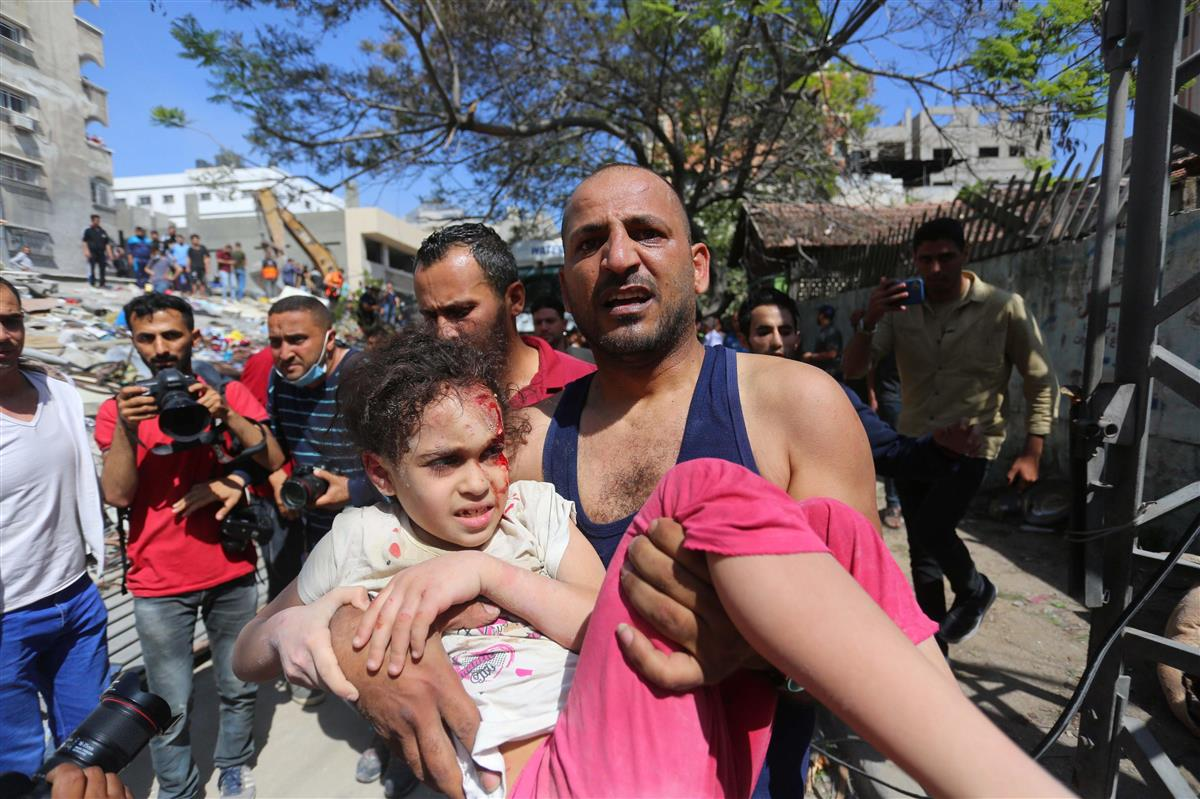 16日、パレスチナ自治区ガザで、空爆により破壊された建物から救助した子どもを運ぶ男性(ゲッティ=共同)