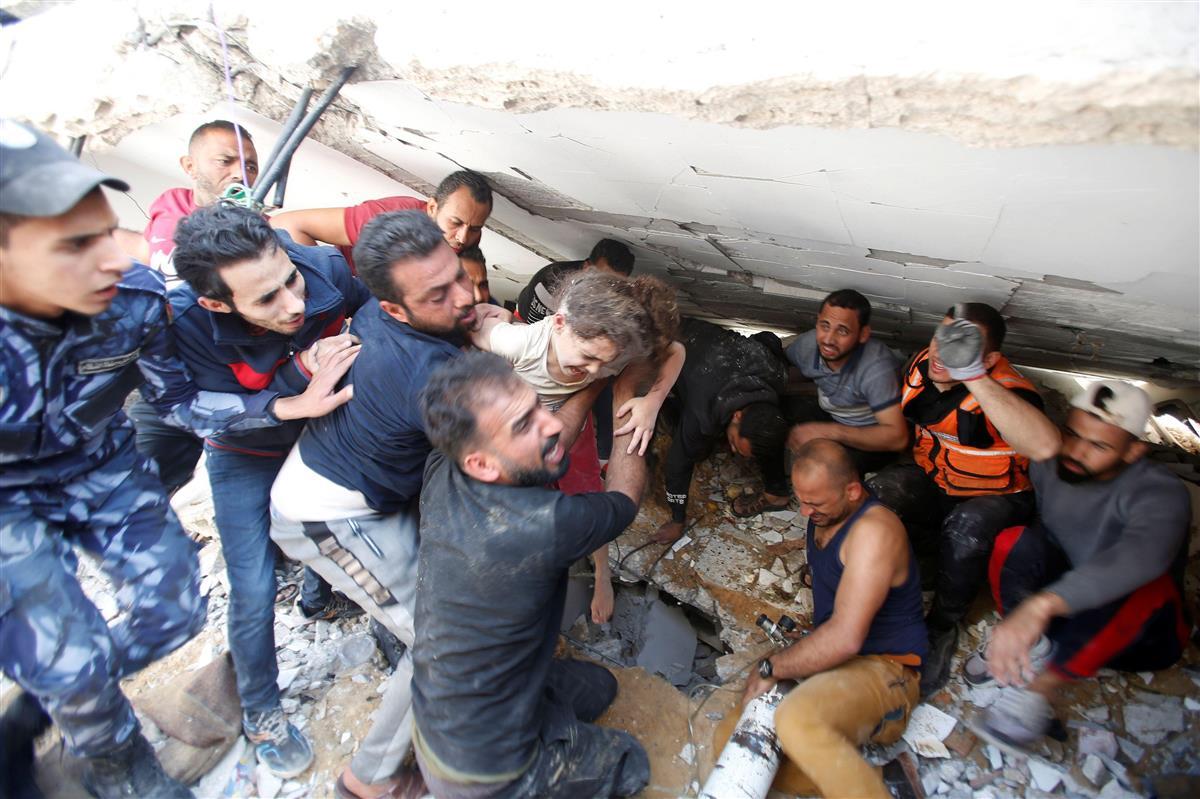 16日、パレスチナ自治区ガザでイスラエルの空爆で破壊されたビルのがれきから6歳の少女を救出する人たち(ロイター)