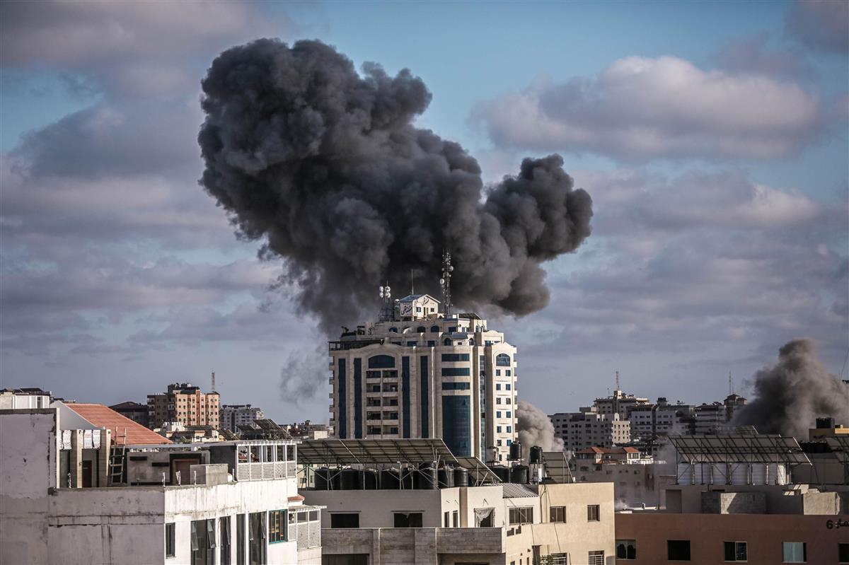 17日、パレスチナ自治区ガザ地区で空爆された建物から上がる煙(ゲッティ=共同)