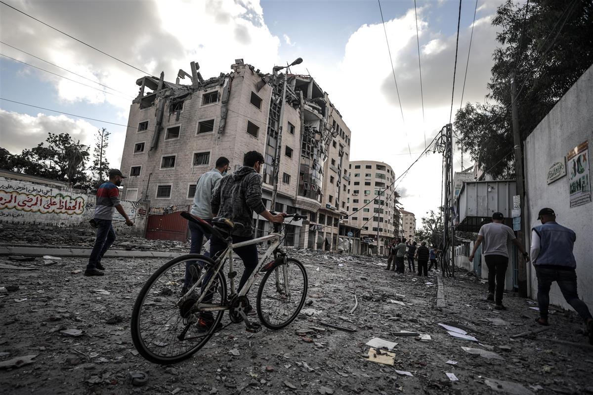 17日、パレスチナ自治区ガザ地区で損傷を受けた建物のそばを歩く人々(ゲッティ=共同)