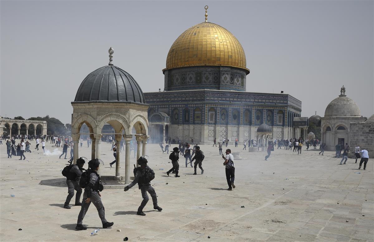 イスラム教礼拝所「アルアクサ・モスク」付近で衝突する、パレスチナ人とイスラエルの警察部隊=21日、エルサレム(AP)