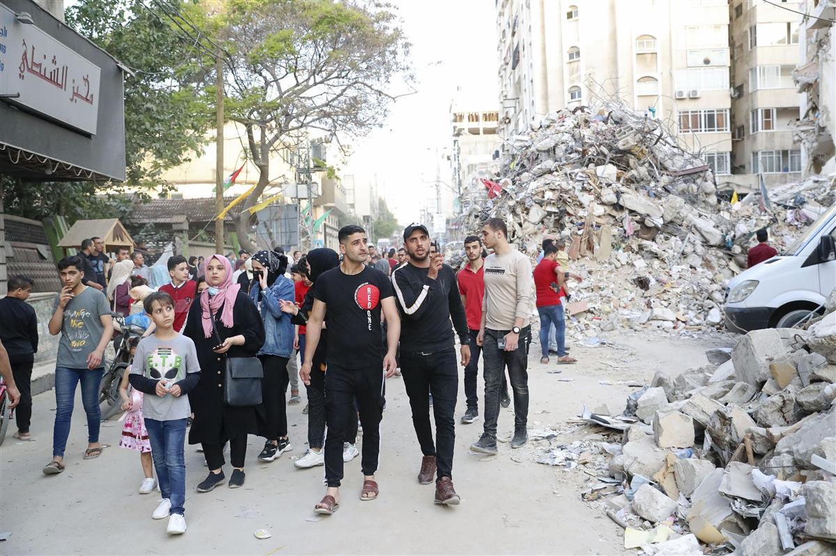 パレスチナ自治区ガザで21日、がれきが積まれた通りを歩く市民(共同)