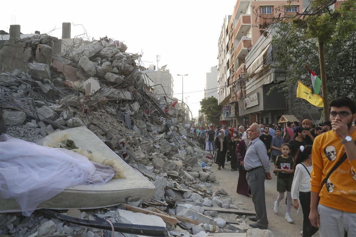 パレスチナ自治区ガザには21日、空爆で破壊された建物のがれきが山のように積まれていた。ウエディングドレスも目に入る(左)(共同)