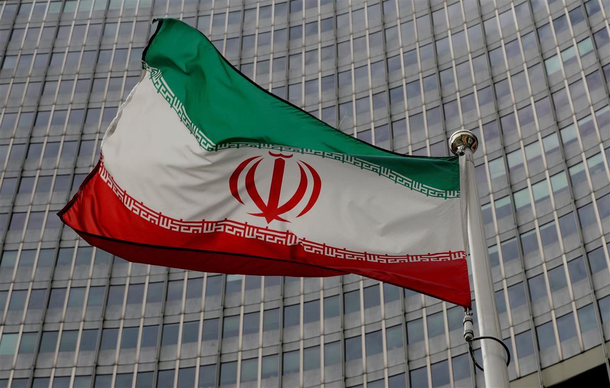 ウィーンにある国際原子力機関(IAEA)本部前ではためくイラン国旗(ロイター)