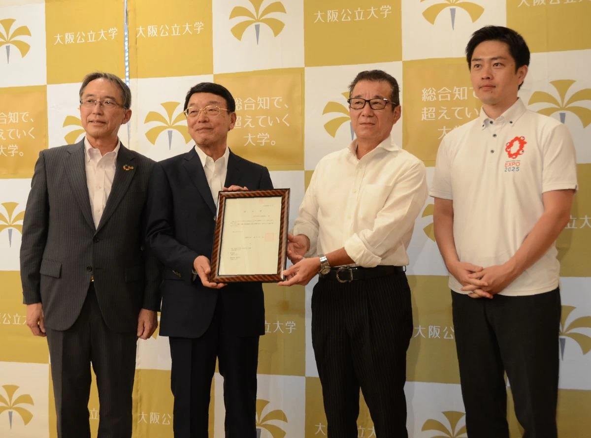 大阪公立大の設置認可の報告を受けた松井一郎大阪市長(右から2人目)と吉村洋文大阪府知事(右から1人目)ら=3日、市役所