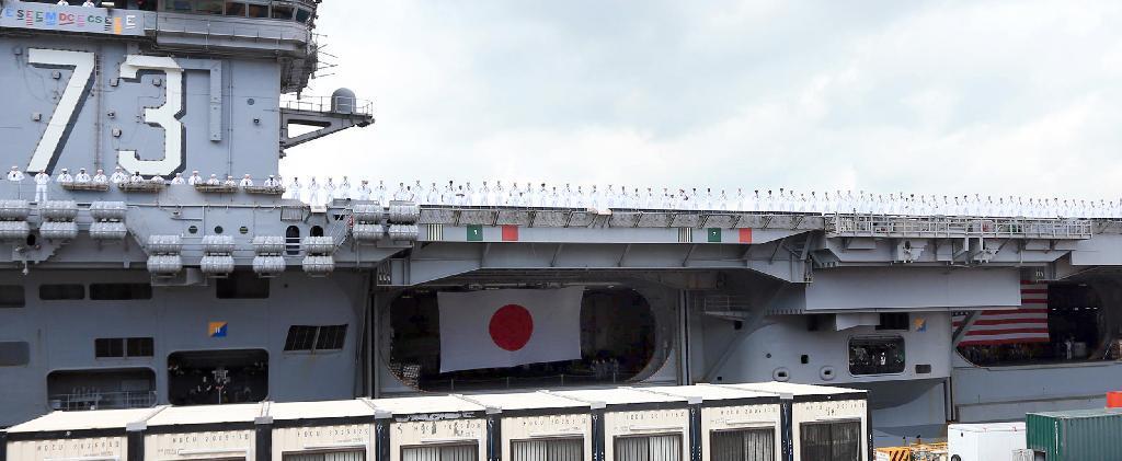 横須賀基地を出港する米空母ジョージ・ワシントン。出港の際には日米両国旗が... 横須賀基地を出港