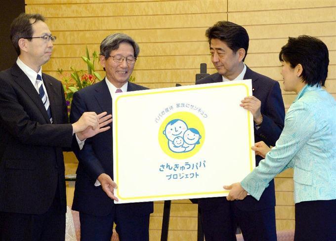 あんきゅうパパプロジェクトのシンボルマークが描か... を手にする(右から)有村治子少子化担当相