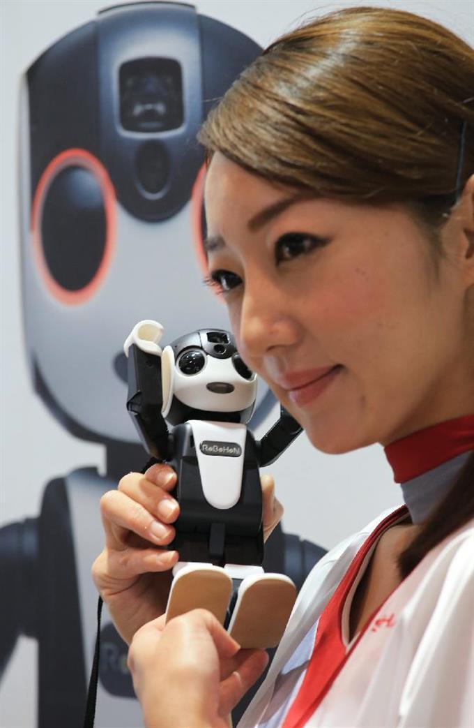 ロボット型の携帯電話「RoBoHoN(ロボホン)」を手にするコンパニオン =6日午後、千葉県美浜区の幕張メッセ(鈴木健児撮影)