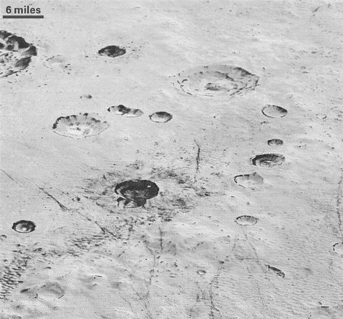いくつもの隕石が落下して穴だらけになった冥王星の氷の平原。できたクレーターの内部には層状になった氷が見える。左上のスケールは約10キロ(NASA提供)