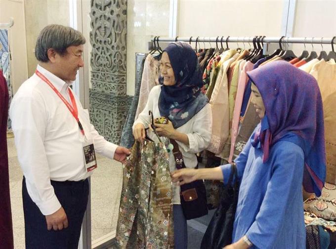 ムスリム女性に着物をリメークした服の説明をする... 画像を拡大する ムスリム女性に着物をリメー