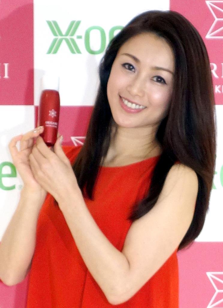 赤い服を着て笑顔で商品をアピールする酒井法子