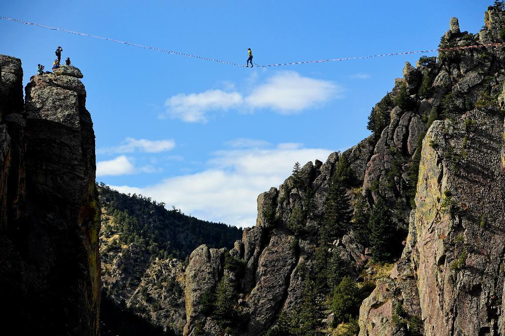 In this Saturday, Oct. 15, 2016, photo, Taylor VanAllen, 24, makes the FA, or First Across, on a high-line from the Wind Tower rock formation to the Bastille rock formation, 450 feet off the ground, in Boulder, Colo. VanAllen, an athlete with Slackline Industries, recreated the Ivy Baldwin high line crossing of Eldorado Canyon in a benefit for trail building at the state park. (Helen H. Richardson/The Denver Post via AP)