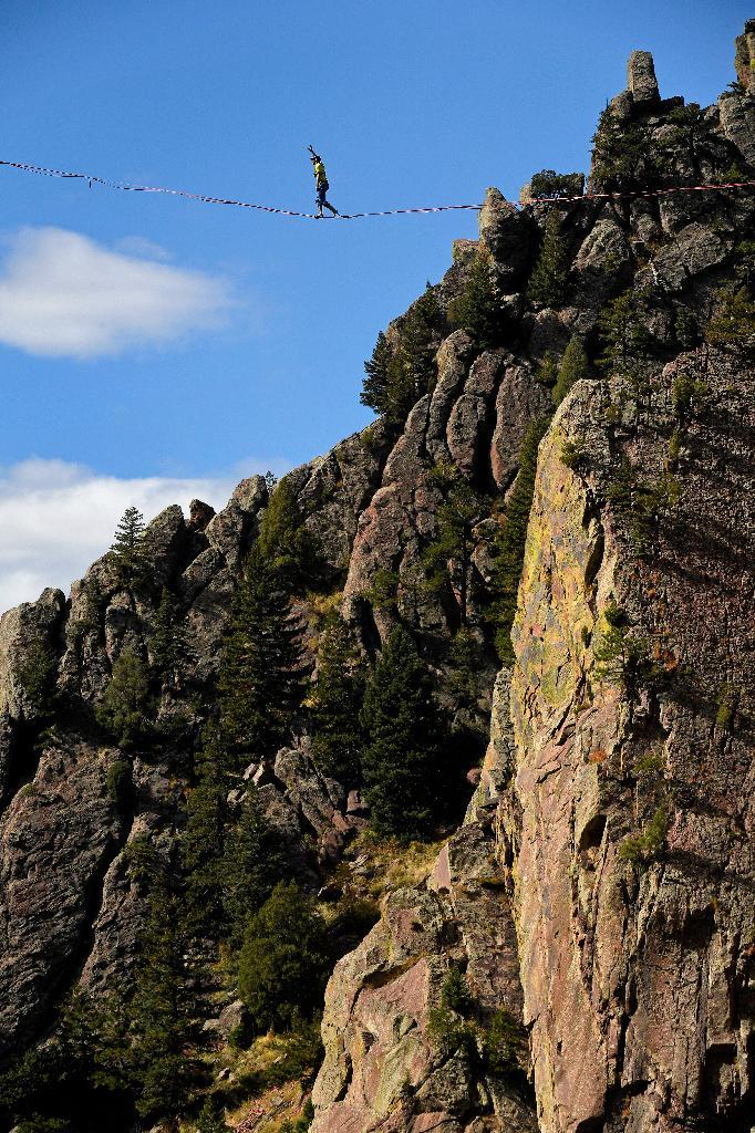 In this Saturday, Oct. 15, 2016, photo, Taylor VanAllen, 24, makes the FA, or First Across, on a high-line from the Wind Tower rock formation to the Bastille rock formation, 450 feet off the ground, in Eldorado Canyon State Park in Boulder, Colorado. VanAllen, an athlete with Slackline Industries, recreated the Ivy Baldwin high line crossing of Eldorado Canyon in a benefit for trail building at the state park. (Helen H. Richardson/The Denver Post via AP)