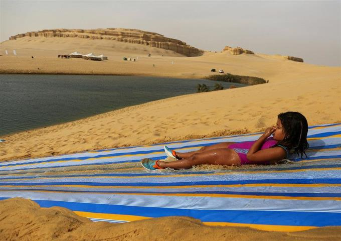 A girl slides down a ramp into the lake in Wadi el-Rayan Fayoum, Egypt, November 18, 2016. Picture taken November 18, 2016. REUTERS/Mohamed Abd El Ghany