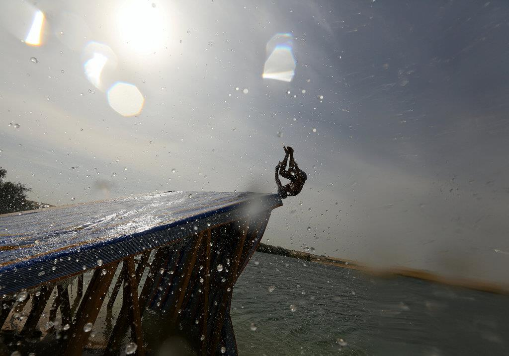 A man slides down a ramp into the lake in Wadi el-Rayan Fayoum, Egypt, November 18, 2016. Picture taken November 18, 2016. REUTERS/Mohamed Abd El Ghany