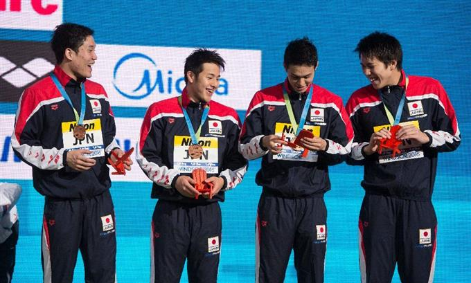 男子200メートルリレーで3位になった日本チーム。Members of the Japanese team admire their gift after receiving their bronze medals for the men's 4x200-meter freestyle relay during medal ceremonies at the FINA World Swimming Championships, Friday, Dec. 9, 2016 in Windsor, Ontario,  (Paul Chiasson/The Canadian Press via AP)