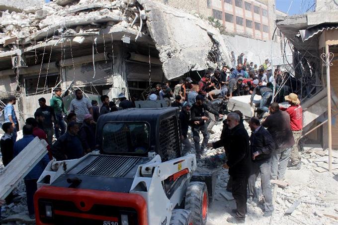 4日、シリア北西部イドリブ県で、空爆後にがれきの中を捜索する救助隊員ら(ゲッティ=共同)