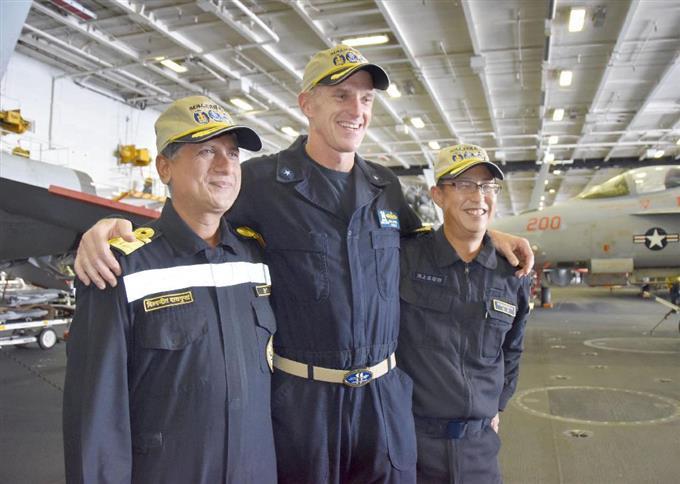 17日、米原子力空母ニミッツの艦内で記念撮影をする海上自衛隊の幹部(右)と米印両海軍の幹部(共同)