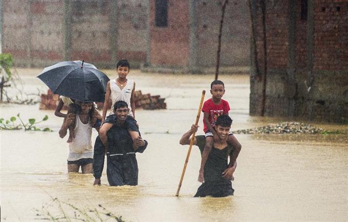 13日、豪雨被害に遭ったネパール南部で、水の中を歩く人々(AP)