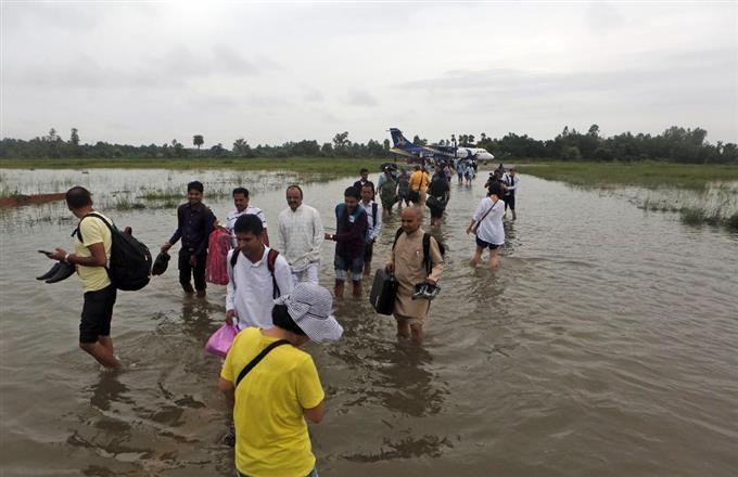13日、豪雨被害を受けたネパール南部の空港で、水の中を歩く利用者ら(AP)