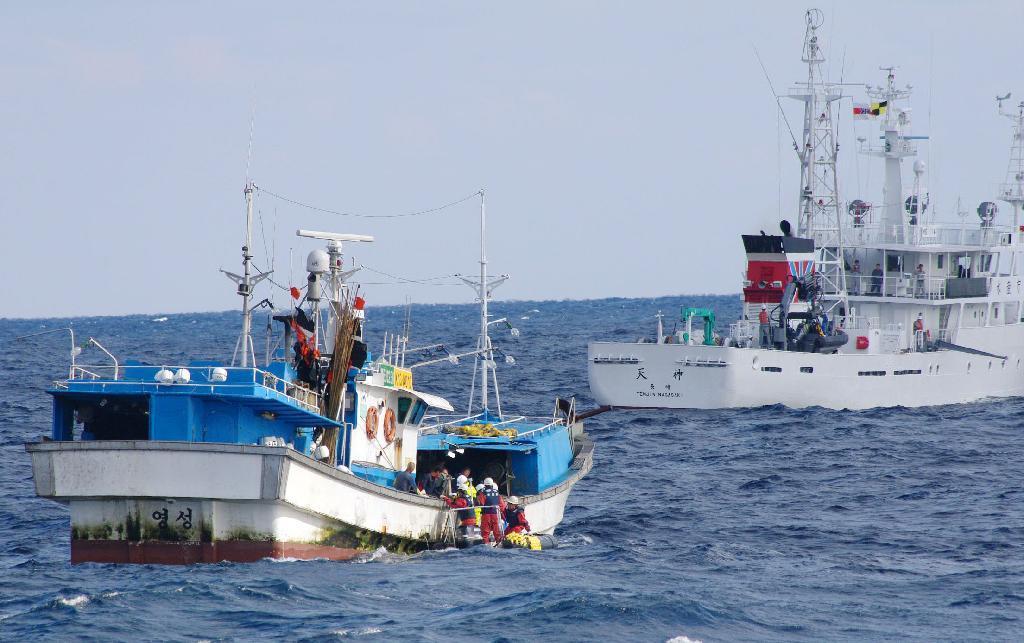 東シナ海で韓国漁船(手前)に取締船(右奥)から立ち入り検査に向かう水産庁の職員=2016年11月(水産庁提供)