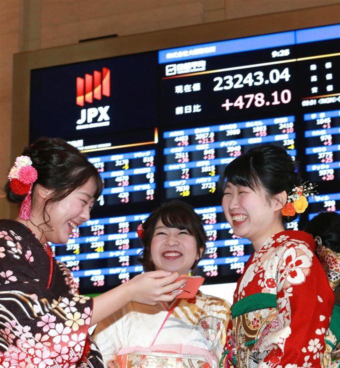 株価ボードを背に笑顔の晴れ着姿の女性たち=4日午前9時25分、大阪市中央区の大阪取引所