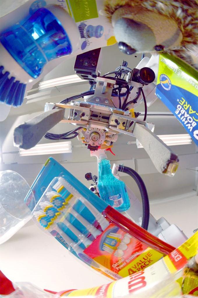 歯ブラシや洗剤を持ち上げる三菱電機が共同開発した仕分けロボット。人間の手のように優しく商品を扱う =兵庫県尼崎市の三菱電機先端技術総合研究所(沢野貴信撮影)