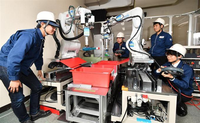 三菱電機が開発した商品仕分けロボット。2本のアームで商品を持ち上げる =兵庫県尼崎市の三菱電機先端技術総合研究所(沢野貴信撮影)