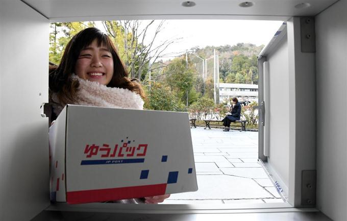 学内に設置された宅配ボックスから荷物を取り出す女子大生 =京都市北区の京都産業大(沢野貴信撮影)
