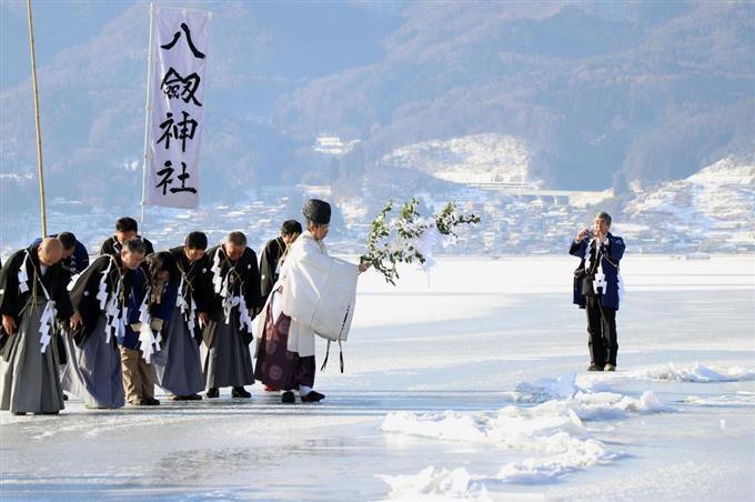 5年ぶりに行われた御神渡りの拝観式で、氷の筋を確認する宮司ら=5日午前、長野県の諏訪湖