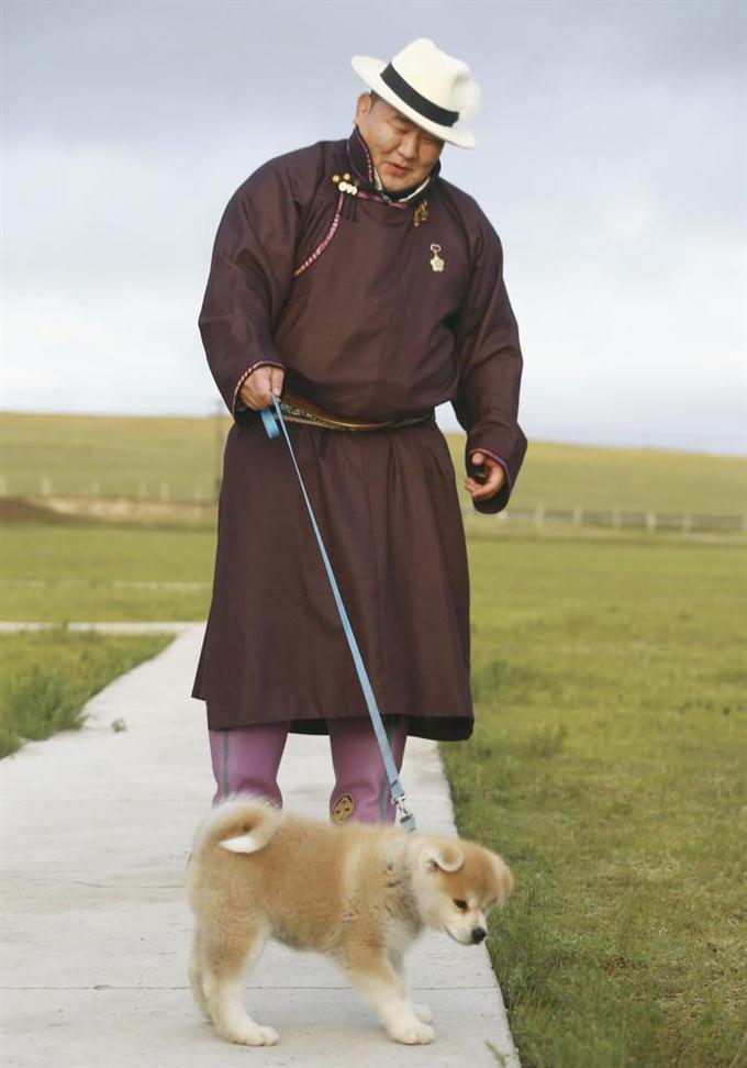 贈呈された秋田犬「マサオ」と歩く大相撲の元横綱朝青龍、ドルゴルスレン・ダグワドルジ氏=10日、ウランバートル近郊(共同)