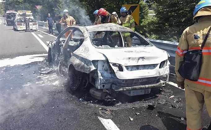 高速道路で炎上したBMW車両の消火活動をする消防隊員ら=2日(江原道消防本部提供・聯合=共同)