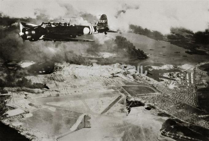 日本軍による真珠湾攻撃。第2波攻撃で爆撃後、ヒッカム飛行場上空を飛ぶ九七式艦上攻撃機。空母「瑞鶴」の艦載機とみられる=1941年12月7日(現地時間)