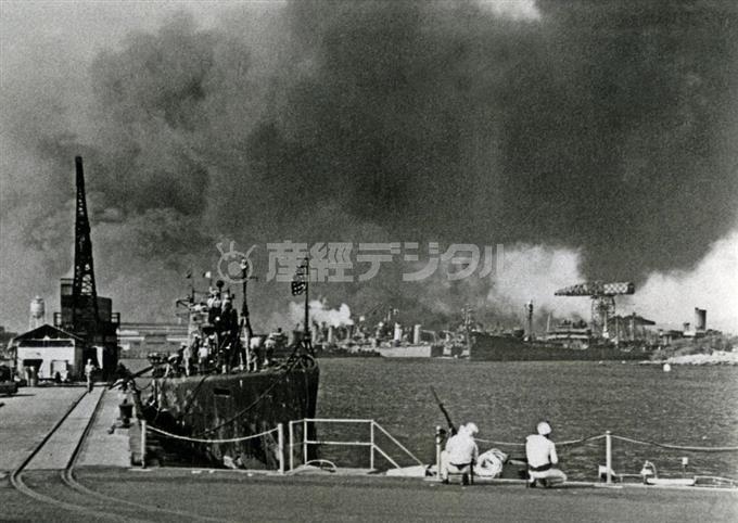 日本軍による真珠湾攻撃。爆撃を受ける海軍工廠で銃を構える水兵