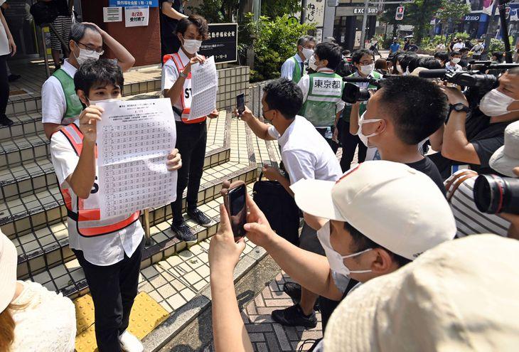 新型コロナウイルスの若者向けワクチン接種会場前で抽選結果を確認する人たち=8月28日正午ごろ、東京・渋谷