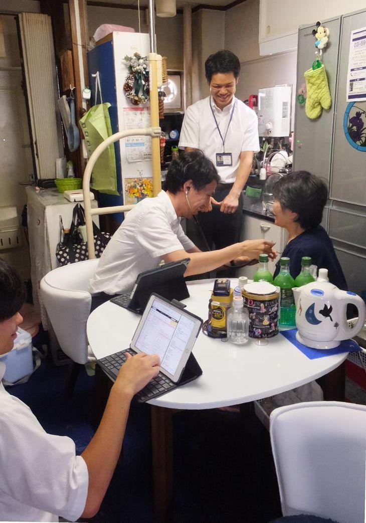 中央の医師と3人チームで動くPA。患者宅での会話を入力(手前)、側に控えてサポートする(奥)=東京都練馬区